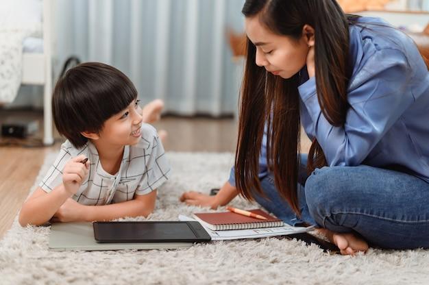 Asiatische mutter arbeitet nach hause zusammen mit sohn. mutter unterrichtet kind für online-lernausbildung. neuer normaler lebensstil und familienaktivität.