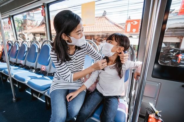 Asiatische mutter bringt ihre tochter zur schule, indem sie mit öffentlichen verkehrsmitteln mit dem bus fährt und eine gesichtsmaske trägt
