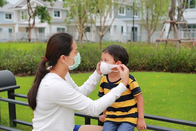 Asiatische mutter der familie, die während des ausbruchs von coronavirus und grippe eine schützende gesichtsmaske für ihren sohn im öffentlichen garten trägt