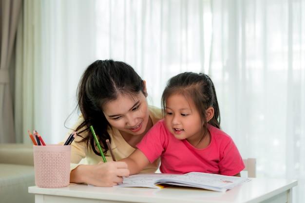 Asiatische mutter, die bei tisch mit ihrer tochter zeichnet zusammen mit farbbleistiften im wohnzimmer zu hause spielt. elternschaft oder liebe und verpfändungsausdruckkonzept.