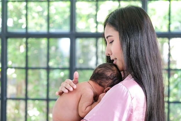Asiatische mutter, die ein neugeborenes baby, lehnend über ihrer schulter hält