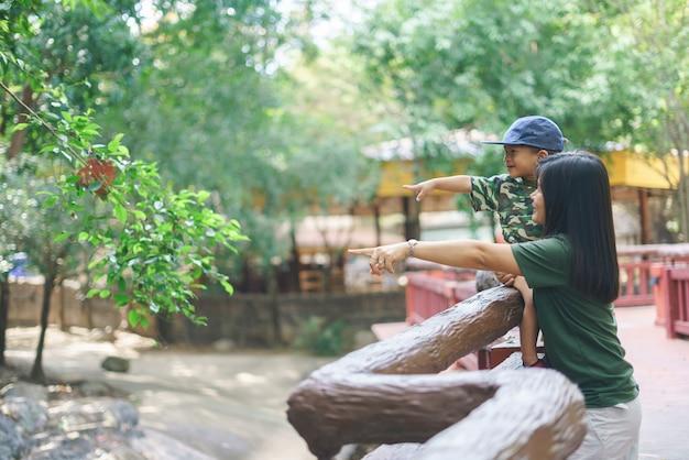 Asiatische mutter, die einen zoo mit ihrem sohn besucht