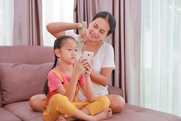Asiatische mutter, die haare für ihre tochter kämmt, während sie zu hause smartphone auf dem sofa im wohnzimmer spielt