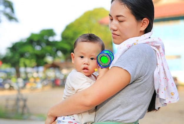 Asiatische mutter, die ihr säuglingsbaby im freien trägt.