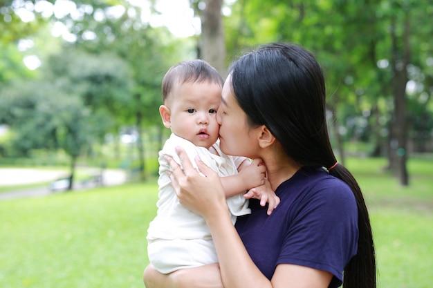 Asiatische mutter, die ihr säuglingsbaby im grünen garten trägt und küsst.