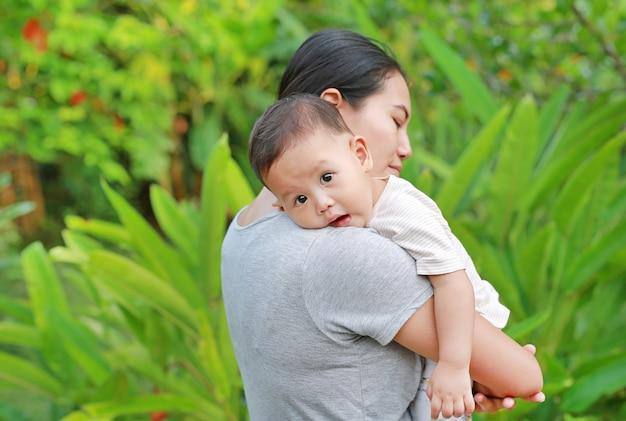 Asiatische mutter, die ihr säuglingsbaby im grünen garten trägt.