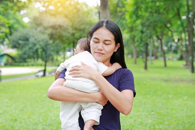 Asiatische mutter, die ihr säuglingsbaby im sommergarten trägt.