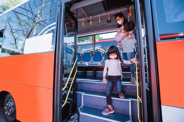 Asiatische mutter, die ihre tochter mit öffentlichen verkehrsmitteln mit dem bus zur schule bringt