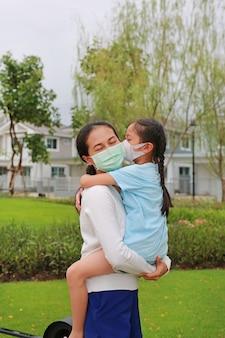 Asiatische mutter, die ihre tochter mit schützender gesichtsmaske und küssen im öffentlichen garten während des ausbruchs von coronavirus und grippe trägt