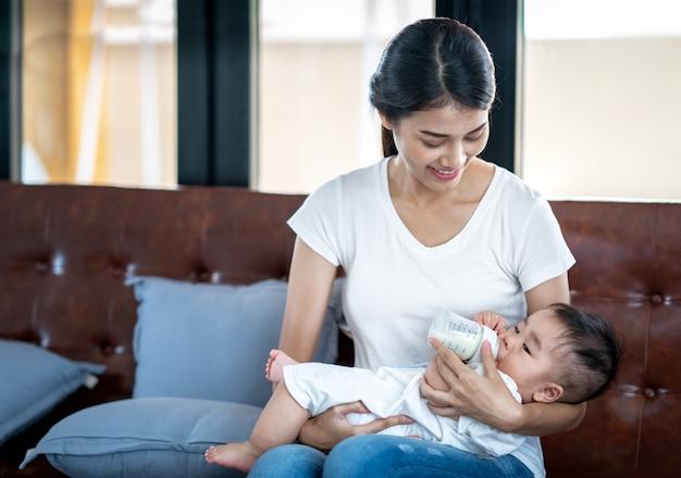 Asiatische mutter, die ihrem baby milch durch flasche füttert