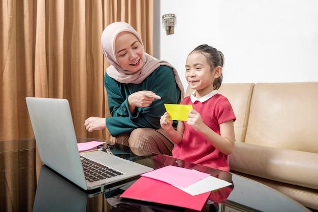 Asiatische mutter, die kleinem mädchen hilft, ihre hausaufgaben mit laptop zu hause zu machen. online-bildung während der quarantäne