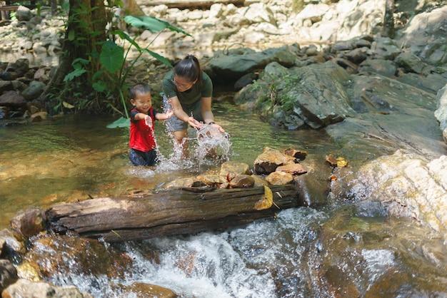 Asiatische mutter, die mit ihrem sohn am wasserfall spielt