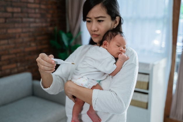 Asiatische mutter, die temperatur zu ihrem kleinen baby misst