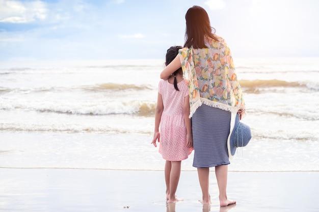 Asiatische mutter, die tochter auf dem strand umarmt