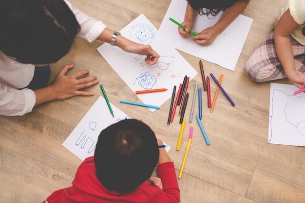 Asiatische mutter, die vier kleine kinder zur zeichnungskunstklasse mit farbstift unterrichtet