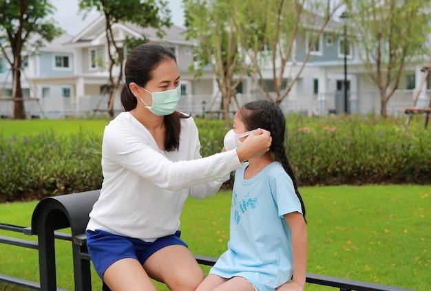 Asiatische mutter, die während des ausbruchs von coronavirus und grippe schutzmasken für ihre tochter im öffentlichen garten trägt wearing