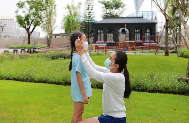 Asiatische mutter, die während des ausbruchs von coronavirus und grippe schutzmasken für kleine mädchen im öffentlichen garten trägt