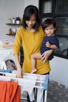 Asiatische mutter eine hausfrau, die kleidung in der waschküche zu hause trocknet und hängt, während sie ihr baby trägt