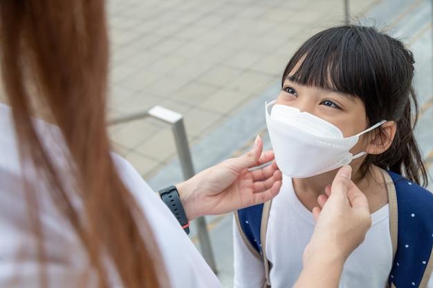 Asiatische mutter hilft ihrer tochter, die eine medizinische maske zum schutz des covid-19- oder coronavirus-ausbruchs trägt, sich darauf vorzubereiten, zur schule zu gehen, wenn sie wieder in der schule ist.