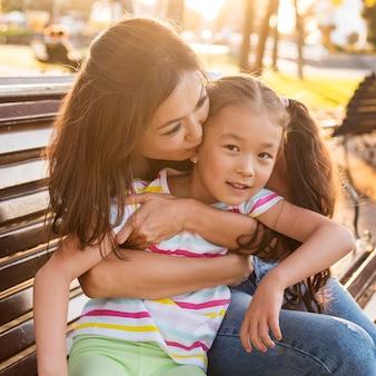 Asiatische mutter küsst ihr kind auf die wange