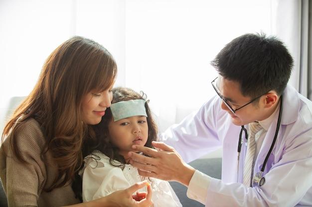 Asiatische mutter nimmt ihre kranke junge tochter mit, um einen arzt im krankenhaus aufzusuchen, und der arzt klebt ein kühles fiebergel auf die stirn des mädchens, das mädchen erkrankt an einem grippevirus. junge patientin wurde krank.