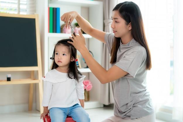 Asiatische mutter schneidet ihrer tochter im wohnzimmer zu hause haare, während sie während der sperrung sicher vor covid-19 coronavirus zu hause bleibt. konzept der selbstquarantäne und sozialen distanzierung.