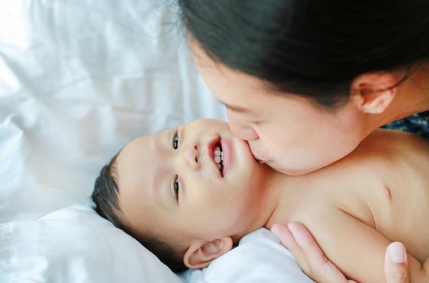 Asiatische mutter spielt und küsst ihr kleines baby auf dem bett.