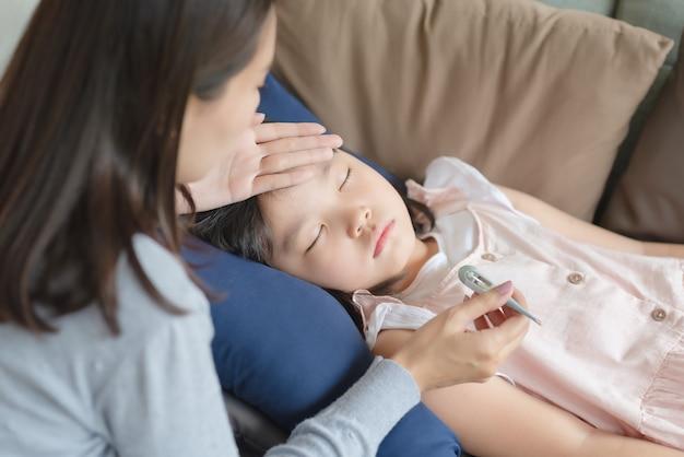 Asiatische mutter überprüft die körpertemperatur ihres kindes mit einem thermometer, das zu hause fieber und krankheit bekam.