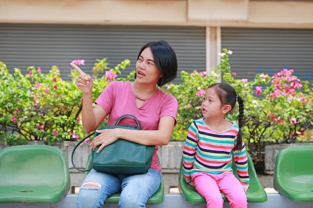 Asiatische mutter und ihre tochter, die am busbahnhof sitzt
