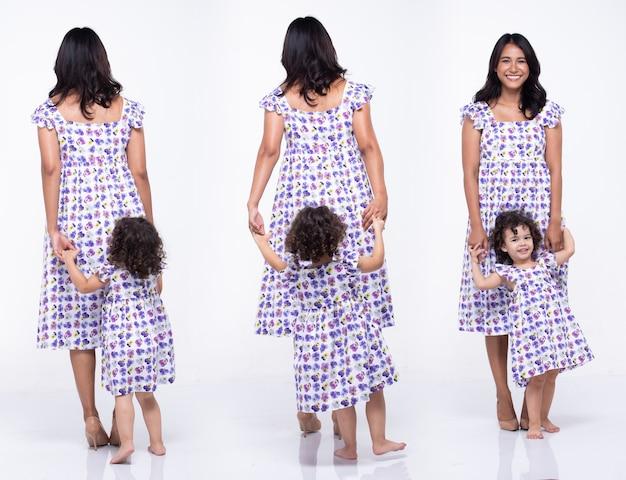 Asiatische mutter und kaukasische tochter stehen zusammen und tragen dasselbe blusenkleid mit lila blumen. kleines mädchen hält mama hand und lächelt mit liebe. weißer hintergrund isoliert