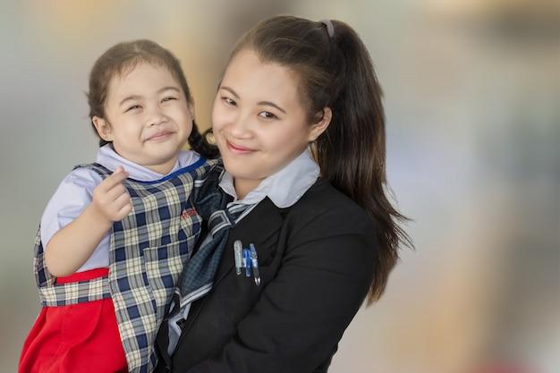 Asiatische mutter und kind, die mit liebe auf unscharfem hintergrund für frohes glückbild der lebensstilfamilie lächelt und umarmt.