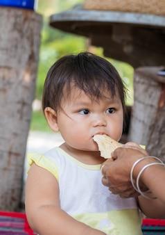Asiatische mutter und kind, die süßigkeit isst