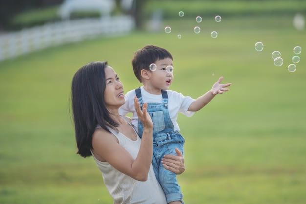 Asiatische mutter und sohn bläst seifenblasen im freien. netter kleinkindjunge, der mit seifenblasen auf sommerfeld spielt hände hoch. glückliches kindheitskonzept. authentisches lifestyle-image.