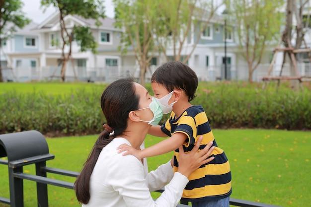 Asiatische mutter und sohn, die während des ausbruchs von coronavirus und grippe eine schützende gesichtsmaske tragen und im öffentlichen garten küssen. sich um die lieben kümmern