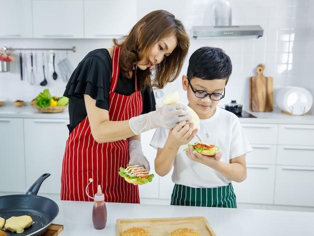 Asiatische mutter und sohn fügen mayo zu frischem burger hinzu, während sie das mittagessen im modernen mittagessen in der küche zu hause kochen. learning by doing des modernen kinderkonzepts.