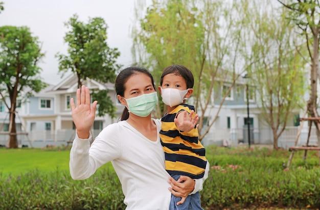 Asiatische mutter und sohn tragen während des ausbruchs von coronavirus und grippe eine hygiene-gesichtsmaske im öffentlichen garten