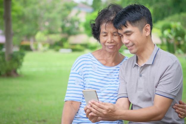 Asiatische mutter und sohn von mittlerem alter, die einen smartphone mit einem lächeln betrachtet
