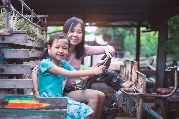 Asiatische mutter und tochter, die auf dem traktor sitzt und smilling ist