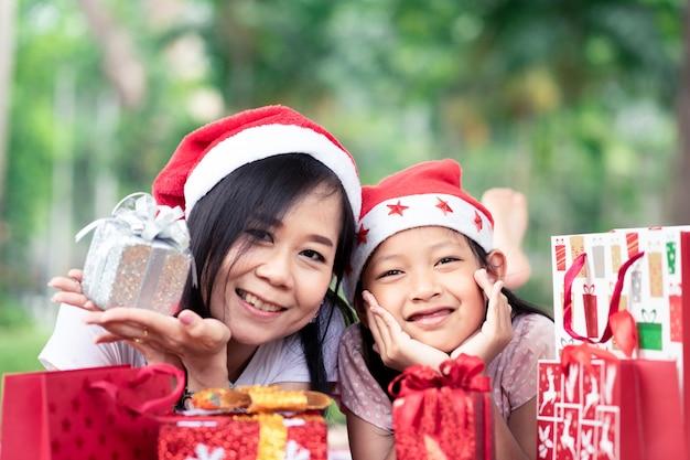 Asiatische mutter und tochter, die mit glücklichem in den frohen weihnachten lächelt