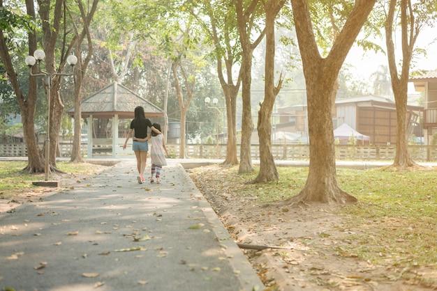 Asiatische mutter und tochter, die zusammen in eine warme umarmung geht. stellt ein gutes verhältnis innerhalb der familie dar, glückliche familienzeit