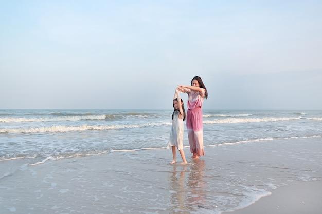 Asiatische mutter und tochter entspannen und tanzen zusammen am meeresstrand in der urlaubszeit.