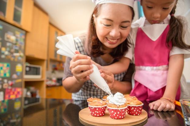 Asiatische mutter und tochter genießen, bäckereikuchen in der küche des wirklichen lebens zu machen und zu verzieren