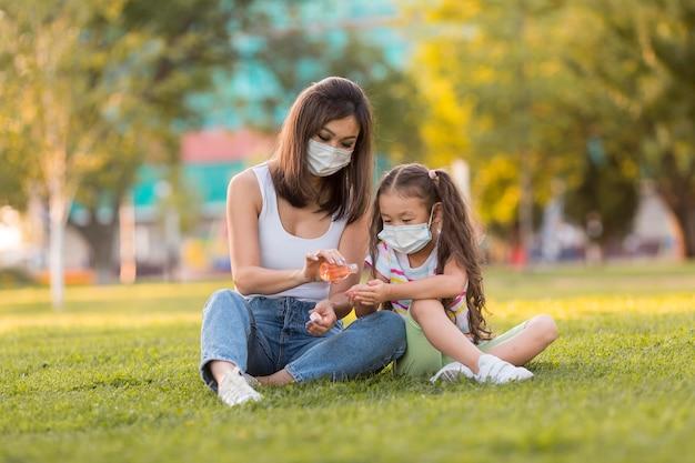Asiatische mutter und tochter mit desinfektionsmittel außerhalb