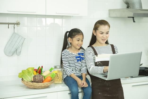 Asiatische mutter und tochter mit laptop in der häuslichen küche