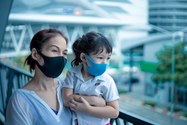 Asiatische mutter und tochter mit medizinischer maske auf der stadtstraße.
