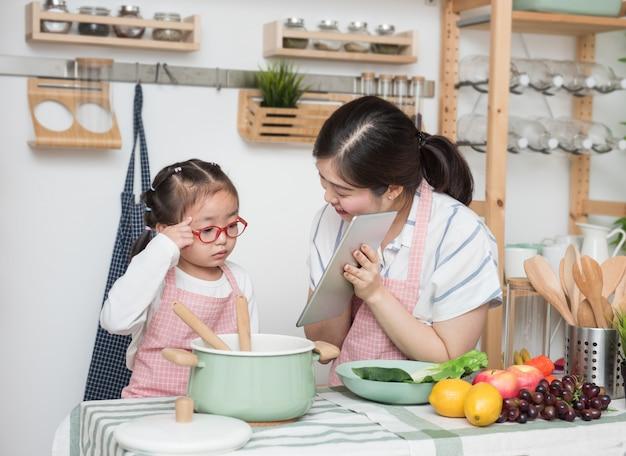 Asiatische mutter und tochter spielen zusammen in der küche, mutter hält tablette, um kleinen mädchen beizubringen, wie man in den semesterferien kocht
