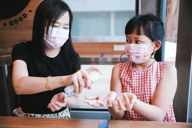 Asiatische mutter und tochter tragen eine maske mit alkoholspray, um das covid-19 zu verhindern