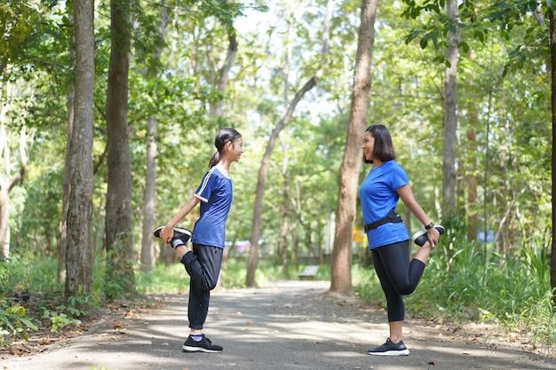 Asiatische mutter und tochter wärmen die oberschenkelmuskeln aus, bevor sie am park laufen