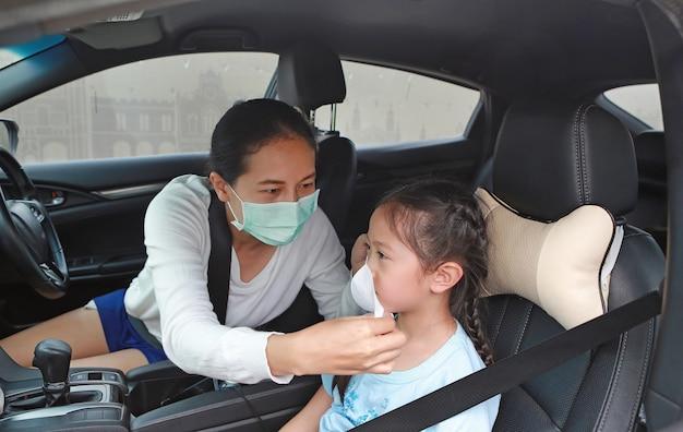 Asiatische mutter und tragen einer hygiene-gesichtsmaske für die tochter, während sie während des ausbruchs des coronavirus (covid-19) im auto sitzt