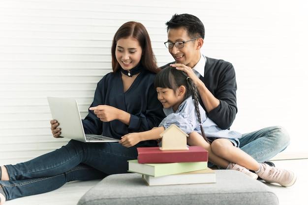 Asiatische mutter und vater der familie mit der tochter glücklich zusammen im wohnzimmer zu hause.